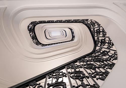 Escalier en marbre et fer forgé d'un bâtiment en loi Malraux